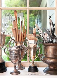 A collection ofantique trophy cups serves as a useful display in this kitchen where they hold spoons and other kitchen utensils: