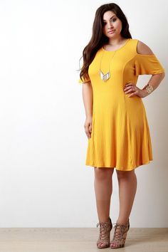 This chic plus size dress features a ribbed knit fabrication, round neckline, cold shoulder detail, and short bell sleeves. Finished with a midi-length hemline. Accessories sold separately. Made in U.