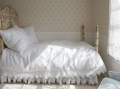 Ashwell credits her British heritage as to why she loves whimsical details, which she showcases in this guest bedroom with patterned wall paper and a pointed lace bed skirt.   - HouseBeautiful.com