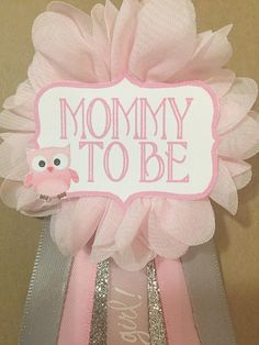 This pin is perfect for any baby shower addition! Can be pinned to any piece of clothing!  Pink flower corsage pin with ribbons from middle: pink satin its a girl, silver glitter, pink satin, gray satin. Choose one: Mommy Mommy to be Grandma Auntie *custom name*  Pink tag with a pink owl. Attached to the back of ribbon is a pin to attach to clothing. This corsage measures approx. 6inches from the top of the flower to the bottom of the ribbons. If you have a specific theme you want the pin to…