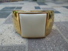 Vintage Avon Bangle. Gold Tone with White Square Feature. Signed. Solid Item in Excellent Condition.  Ask a Question $14.00 USD
