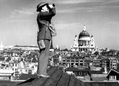 An aircraft spotter on the roof of a building in London, England, with St. Paul's Cathedral in the background. (National Archives)