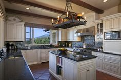 like the pot rack and the exposed beams and the style of cabinets, still would want dark wood cabinets as well