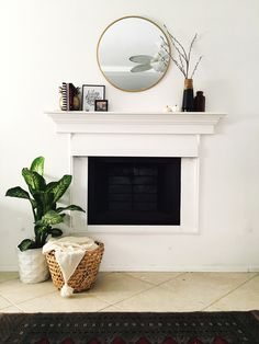 White fireplace with round brass mirror over mantle decor