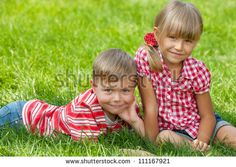 A boy and a girl are resting on the green grass in summer