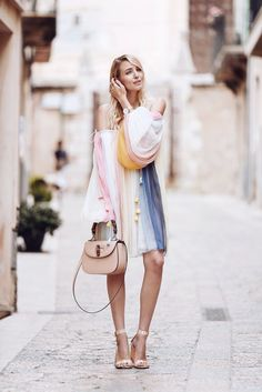 A billowy ombré dress in soft pastels with nude heels and a matching satchel.
