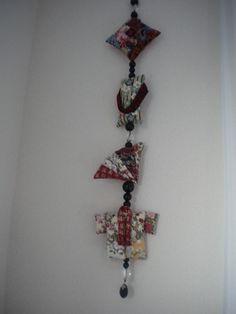 Een handgemaakte muurslinger met Japanse stoffen ornamentjes. Tussen de ornamentjes zijn zwarte en doorzichtige kralen geregen.  Met deze muursling...