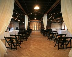 This space integrates many things well: The ceremony and the reception; the solid brick and wood with the soft fabric; the black and the white mitigated by the cream. A well-balanced space.