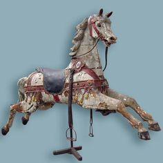 """Hubner - $4200  Rare late 1800s German jumper in distressed old dry paint. The horse features a finely delineated head with a sweet open-eyed expression on an unusually elongated and gracefully carried neck. Noteworthy are the trappings composed of applied bentwood, the dozen or so metal applique tassels and jewel keepers, the mirrored escutcheon on the neck strap and the upholstered saddle stuffed with horsehair. The outstretched forelegs retain the original attachments for the """"rocking…"""