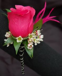 Make a Boutonniere - FREE TUTORIALS http://www.wedding-flowers-and-reception-ideas.com/boutonniere-tutorials.html  ......Hot pink rose with clusters of white waxflower and backed with green ruscus leaves.  Accent with hot pink feather.  Stems are single taped, wrapped with black ribbon and overlay of crossed silver metallic wire.