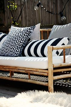 {nautical patio} black and white and navy striped pillows on simple patio furniture with woven blankets