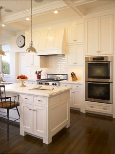 White Kitchen - Shaker cabinets, marble counters, subway tile, stainless appliances, dark wood floor.
