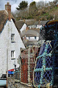 Crab and lobster pots await their next use in the spring sunshine among the thatched cottages of Cadgwith Cove in Cornwall