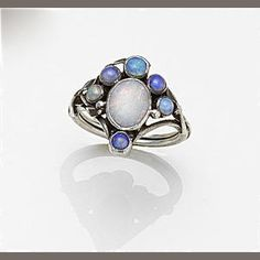 Rhoda Wager (attrib.). Arts and Crafts ring. Silver and opal, the central oval opal collet to a kite-shaped mount set with five smaller circular opal collets, wires, beads and leaves. Ring size P, unmarked. Sold by Bonhams.