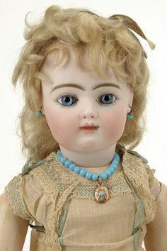 """France, ca. 1885, pale bisque socket head incised R 1 D, stationary blue paperweight eyes, closed mouth, finely painted brows and lashes, pierced ears with original earrings and matching necklace, blonde mohair wig with cork pate, 8 ball jointed French composition body with straight wrists, wearing original aqua and cream lace chemise, 18"""" t."""