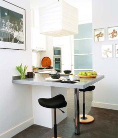 UNA MESA EN EL MÍNIMO ESPACIO Es una prolongación de la encimera de Silestone gris –lo que da homogeneidad– y se apoya en una pata de acero. El hueco bajo ella se aprovecha con un módulo de armario y, además, para recoger los taburetes Move de Stokke. Como iluminación, una lámpara de Noguchi comprada en Mosel. El mobiliario, un diseño de la interiorista Concha Rodríguez, es de Bell House.
