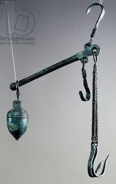 Steelyard balance with bronze hook for hanging goods to weigh and acorn counterweight decorated with stripes at top, artifact uncovered in Pompeii, Campania, Italy, Etruscans Civilization, 1st century. Naples, Museo Archeologico Nazionale (Archaeological Museum)