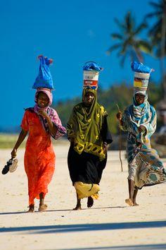Three Local Women Walking on Kiwengwa Beach Zanzibar after a day's work harvesting seaweed.
