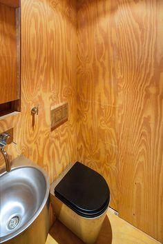 MIN | MINIMOD - MAPA - MAAM + STUDIO PARALELO. Plywood bathroom with wall mounted steel toilet.