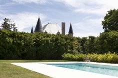 Swimming pool goals: inspiration for at-home summer relaxation: The heated outdoor pool of fairytale château, Les Trois Garconsis surrounded by lawns and hedges for year-round relaxation.