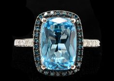 A 10K white gold blue topaz and diamond ring composed of a 12 × 8 mm carat rectangular cushion cut blue topaz, framed with .25 carat total weight treated blue diamonds, flanked by white diamonds on...