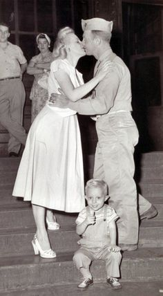 A family reunited after the war (love her hair and dress and shoes!!)