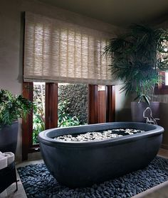 Beautiful basalt tub placed in a bed or river rocks - Decoist