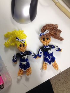"CHEERLEADERS. Designed and loomed by Amber Battle Shebesta on the Rainbow Loom. Inspiration from MarloomZ Creations and PGs Loomacy. Amber said: ""Cheerleaders that I made for my daughter and her friend They even had poms and megaphones (not shown)."""