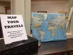 """""""Map Your Travels"""" public library display - with a map on a corkboard and pins alongside a travel book display. Great for January - patrons  can map where they've been in the previous year and where they are going in the coming year."""