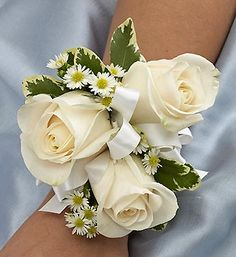 Blue and White Corsage  Elegant white roses, white Monte casino and variegated pittosporum laced with white ribbon creates an elegant accompaniment for the mother of the bride or groom, grandmothers, or treasured relatives. $25.00