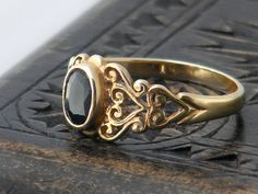 A romantic 9ct gold ring from the late Victorian period with intricate shoulders of gold scroll work supporting a glossy black collet set stone.