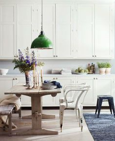Green pendent light, rustic table, white cupboards love