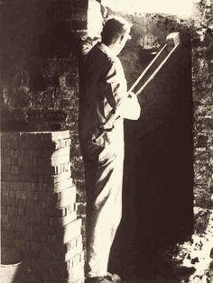 """Gottfried Kuckertz zieht den Kontrollstein am Feuerloch des Kasseler Ofens. Temperaturanzeiger gab es nicht. Mit geübtem Blick in den gelb-weiß glühenden Ofen schätzt der Töpfermeister die Ofentemperatur und ob er """"durch"""" ist. Aufnahme aus dem Jahr 1942."""