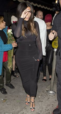 Looking glam: The reality star stuck to her signature black for the fun night out, teaming a high waisted skirt in a stretchy fabric with a semi sheer top, which flashed her black bra