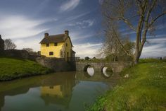 Stogursey castle cottage, moat and drawbridge ~ England... a bit like a John Constable painting :)