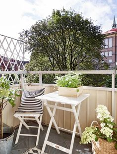the white table and chair are really cute in this tiny outdoor space