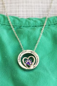 "Though your beloved pet may no longer be at your side, the memories shared will always have a special place in your heart. Our petite silver pendant reflects the sentiment, with a heart encapsulated in an eternal circle, a purple paw held within and the engraved phrase ""Once by my side... Forever in my heart™."""