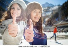 Happy multiracial women going to ice skating outdoor with thumbs up gesture. Holding skates shoes. Healthy lifestyle and winter sport concept at sports stadium, mountain landscape