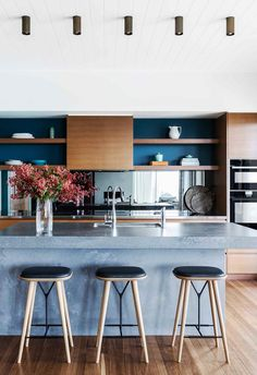 The kitchen in this renovated beach house features a concrete island bench, timber joinery and a mirror splashback.