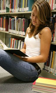a young woman reads a book in a library aisle