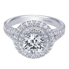 Wow!! Double round halo engagement ring with a split shank band and shared prong diamonds in the band.