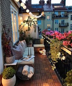 Beautiful narrow balcony with parquet floor, sectional sofa, blanket basket, string lights, and flowering planter boxes.