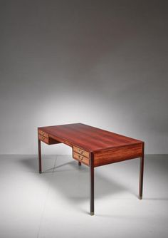 A large rosewood veneer desk, by Danish designer Ole Wanscher and produced by A. J. Iversen. The desk has four drawers with brass handles and the legs have brass socks.