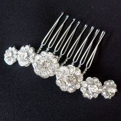 Gorgeous delicate hair comb in a dainty daisy design.These floral styled hair combs in silver with clear crystal are perfect for adding a little glamour to your outfit. Lovely for an evening or a special occasion, a lovely finishing touch. Or use as beautiful bridal combs, which will easily complement any bridal outfit. Please note that these items are supplied in an organza bag.Silver metal, clear diamantes.7 x 1.5cm approximately.