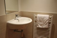 White Wall Mounted Sink In Front Of Beige Tile