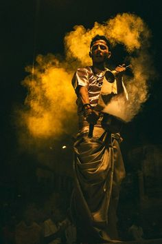 Man performing Ganga Aarti in Varanasi by Mitchell Kanashkevich