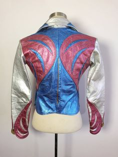 ABOUT: RARE AS F vintage late 1960s early 1970s East West Musical Instruments Parrot Jacket in a mind blowing Ziggy Stardust-eat-your-heart-out silver, pink and blue. Incredibly heavy weight leather with thick metal zipper up the front and matching slit zipper pockets at the side. SIZE: XS. Please refer to measurements for accurate fit. We can not be responsible if an item does not fit. Please compare the measurements below to a like item in your closet which already fits in order to ensure…