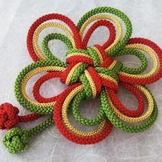 日本伝統工芸の組紐を使い、伝統のうめ結びを朱赤、金色、ターコイズグリーン(深緑)の組紐を3本使い結びました。特に、赤、緑系の色の入ったお着物に映える色目です。他にない組紐の上品なオリジナルの髪飾りです。紐の端は、縁起の良い釈迦玉をほどこしました。同色の紐はすべて繋がって結んでいます。最後の写真は、色違いです。大きさ、雰囲気の参考になさって下さい。裏は、バレッタを縫い付けています。*色違いも、あります。和装の時に使わなくなりましたら、バレッタをブローチに代えて使うこともできます。サイズ 約直径11cm