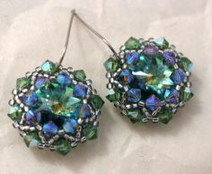 "Faceted green and blue Swarovski rivoli stones are wrapped with sparkling green crystals and silver seed beads. The crystals are super sparkly and have flashes of blue and purple. They are attached to stainless steel earwires and measure 1.25"" long. Via Etsy"