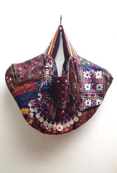 molina  The carry all bag, handmade with vintage and antique mixed woven textiles. Fabric colors comprised of navy blue and multi embroideries. 3 button snap closure. By Simone Camille.